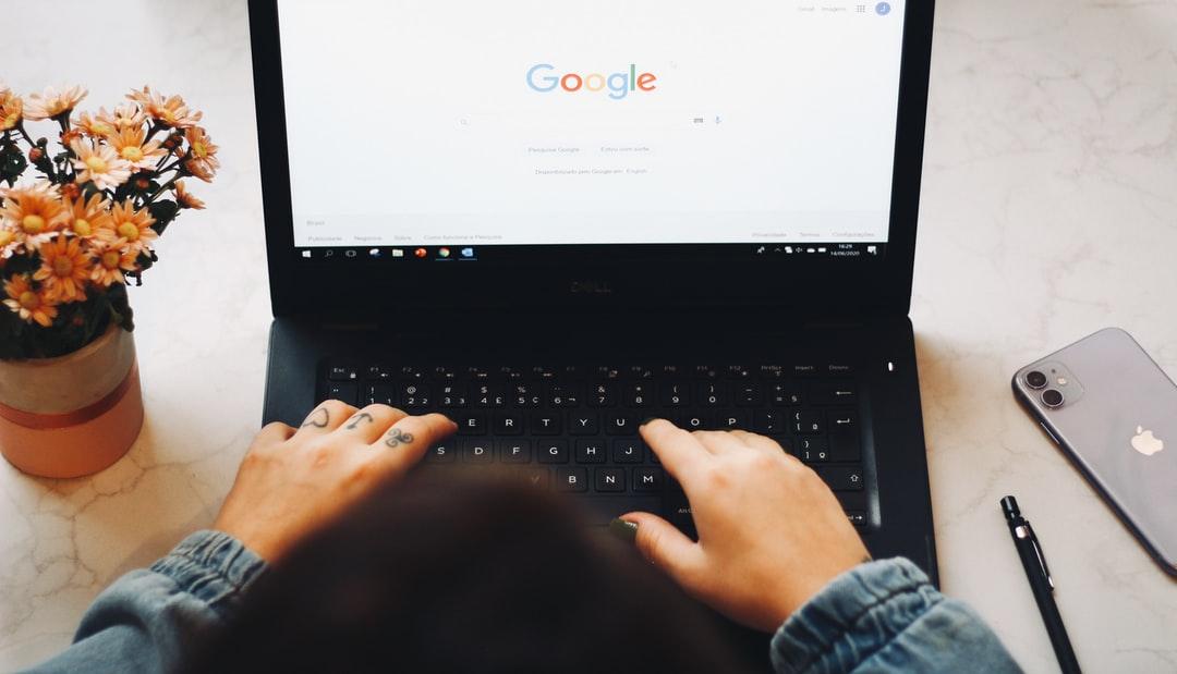 Person sitzt vor Laptop und nutzt Google