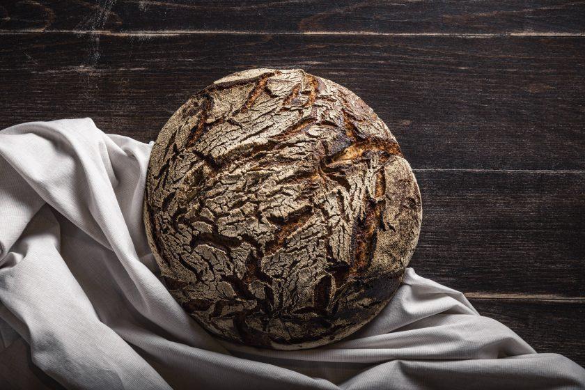 Ein Laib Brot auf einem Tuch liegt auf einem dunkelbraunen Holztisch