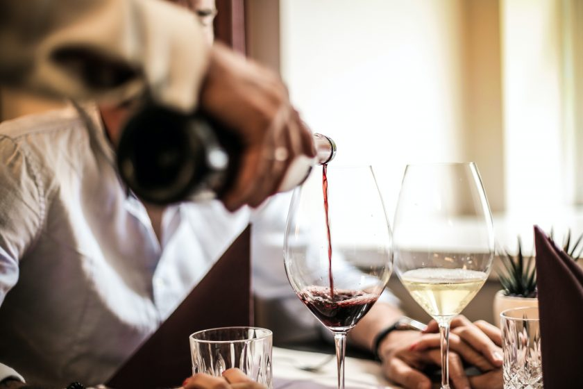 Kellner gießt Wein in ein Weinglas ein