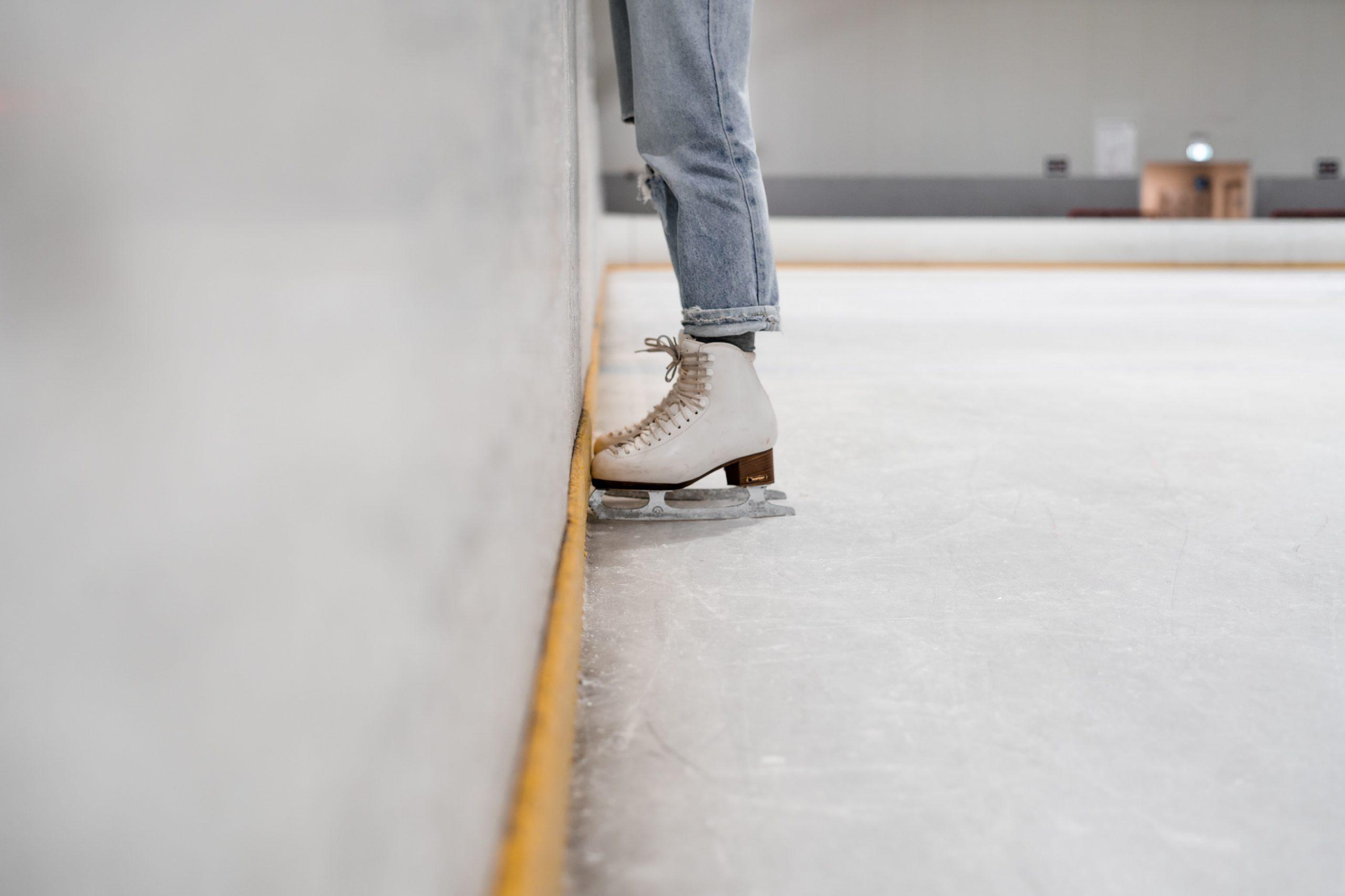 Eine Person steht mit Schlittschuhen auf einer Eisbahn. Es sind nur die Beine und die Schuhe der Person zu erkennen.