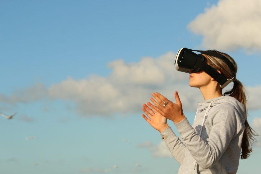 Eine Frau mit VR-Brille blickt in Richtung eines blauen Himmels. Sie hält beide Arme gebetsartig nach oben.