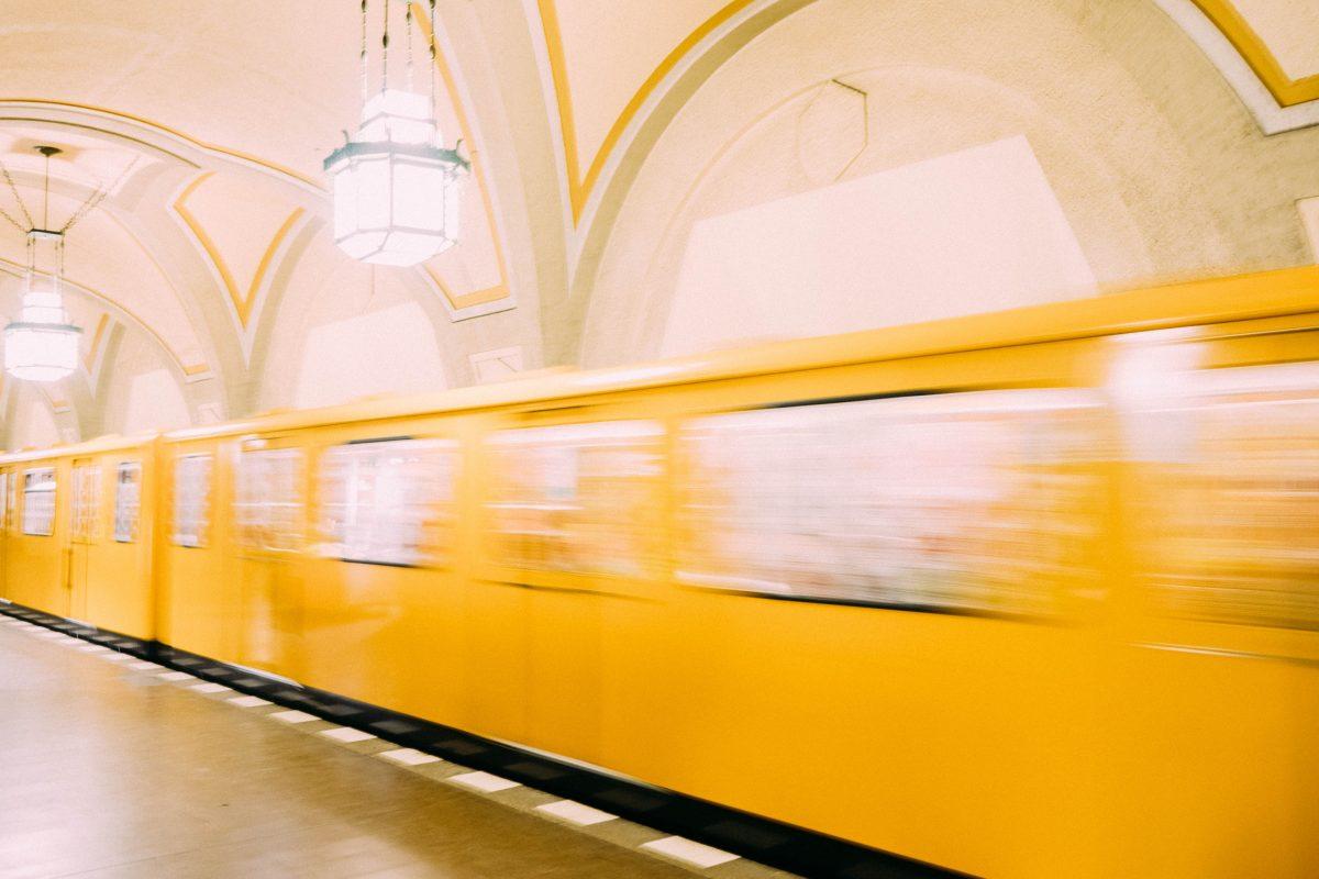 Eine gelbe U-Bahn in Berlin fährt durch den Bahnhof.