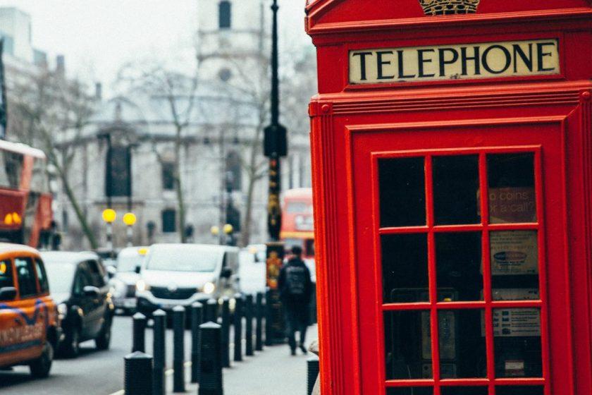 Eine rote Telefonzelle steht am Straßenrand in London.
