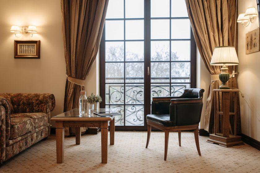Ein Stuhl, ein Tisch und eine Couch vor einer Fensterwand