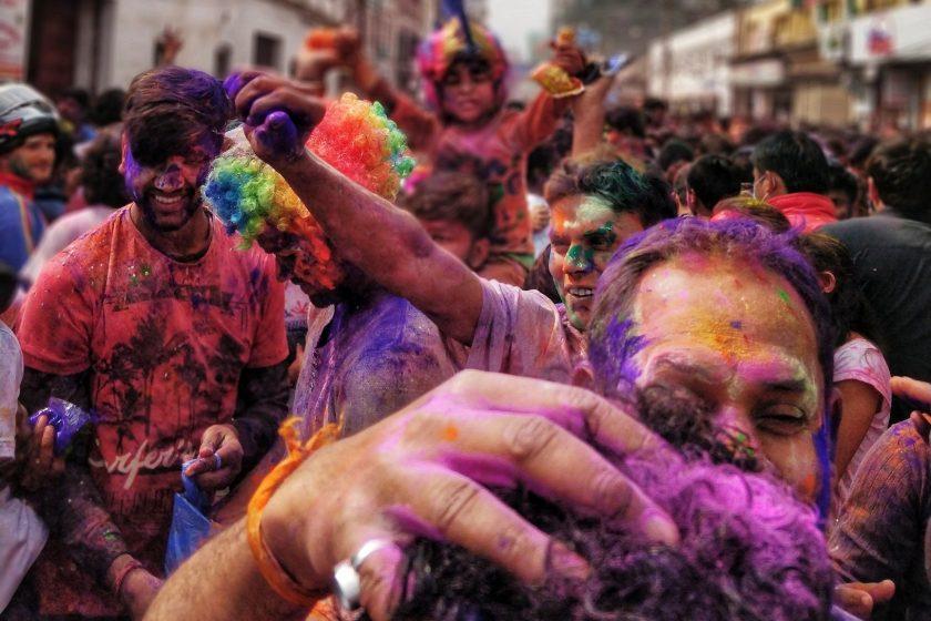 Eine große Gruppe von Menschen ist mit bunten Farben bedeckt und umarmt sich.